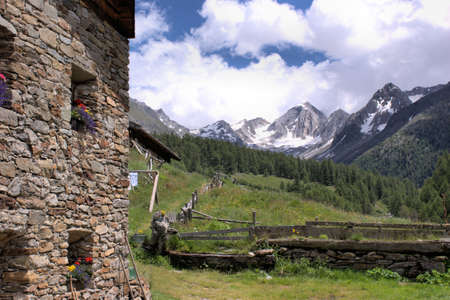 In the Pfossental, South Tyrol; part of an old farmhouse with stone walls, snow-capped mountains in background