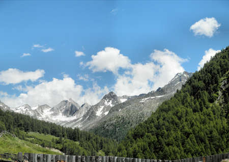 In the Texel Group Nature Park; looking over the fence to the snow-capped mountains of the Oetztal Alps in South Tyrol, Italy; blue sky and white clouds