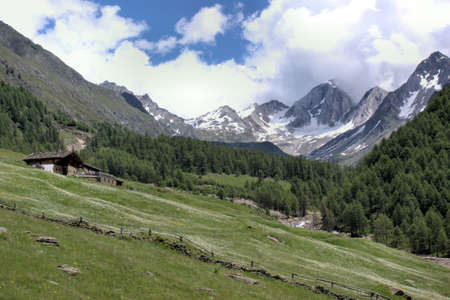 The Pfossental in South Tyrol in summer. Rocks, forested slopes and snow-capped mountains, a mountain hut and a blue sky with white clouds