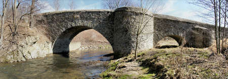 Imposing stone arch bridge over the Great Striegis in Saxony, Germany; barren landscape in spring, bare meadows and trees, blue sky with white clouds, panoramic image