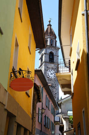 Narrow alley in Ascona in Ticino, Switzerland, overlooking an old church, cloudless sky