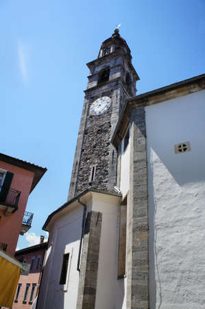 View from the frog perspective to a church tower, narrow streets in Ascona in Ticino, Switzerland