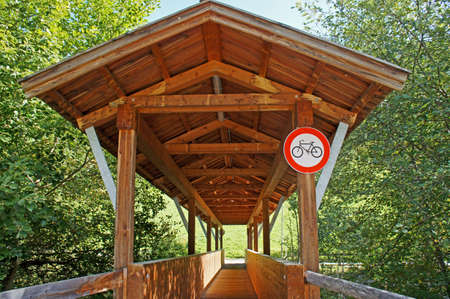 Roofed wooden bridge only for pedestrians and a prohibition sign for bicycles