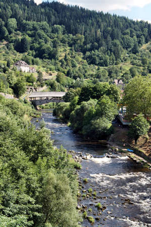 Wildly romantic Murg Valley in the northern Black Forest, wooded mountain slopes and a roofed wooden bridge over the river