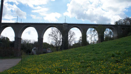 View on a viaduct of the railway in Saxony in Germany; meadow in spring and blue sky with clouds,