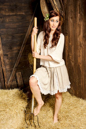 Young woman with fork in the barn
