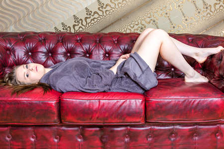 Woman is lying on the sofa and looks expressionless