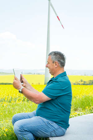 Man with tablet PC on the canola field with wind turbine