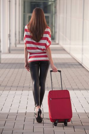 woman pulling her luggage on the street