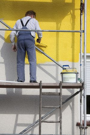 man on a scaffold painting house with roller