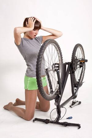 woman in trouble looking at her defect bicycle