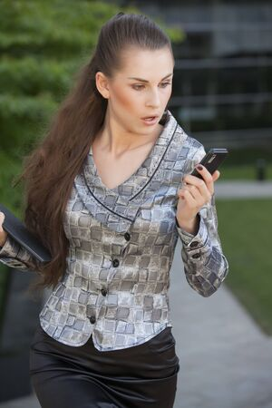 young businesswoman looking surprised on cell phone outdoor