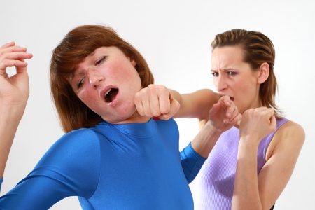 women fighting - face punch over white backgroundの写真素材