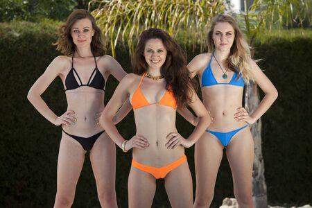Foto de Three smiling fitness bikini girls posing by the swimming pool - Imagen libre de derechos