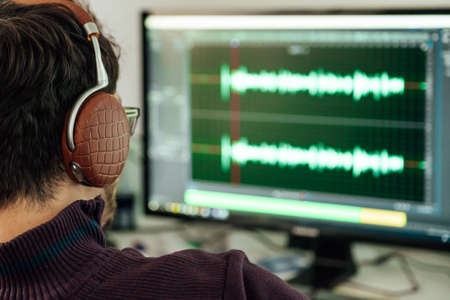 Photo for The man in the photo studio records and modifies singing, voice and music for commercial use. Works in an audio editor in a computer with headphone - Royalty Free Image