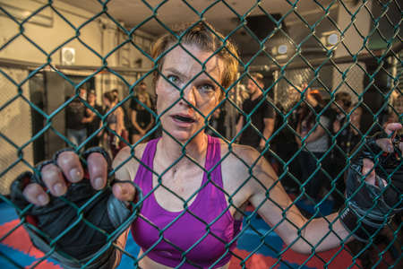 Photo pour Gorgeous woman, mma fighter in gym during training. Preparing for a hard caged match. Sexy fighter girl punching actively. Aggressive and ready to fight. - image libre de droit