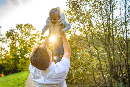 Photo pour Happy dad with daughter enjoying autumn in park at beautiful weather - image libre de droit