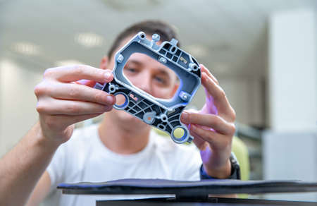 Quality engineer examines a sample scanned with a laser on a 3d scan in a research laboratory