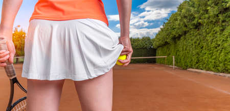 Photo for tennis ball in a womans hand in a skirt on a tennis court. preparation for serving a balloon in tennis - Royalty Free Image