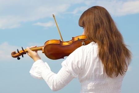 Young woman playing violin on sky background