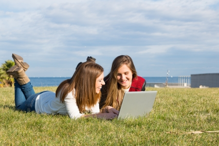 Girls in a park with a laptop at information