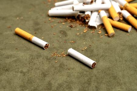 Photo pour Fight against smoking. Cut cigarette on a green background - image libre de droit