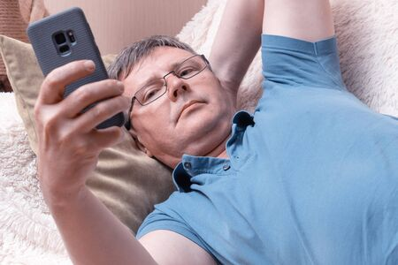 Photo pour A man with glasses looks at a smartphone while lying in a cozy sofa. Middle-aged businessman checks mail in a smartphone - image libre de droit