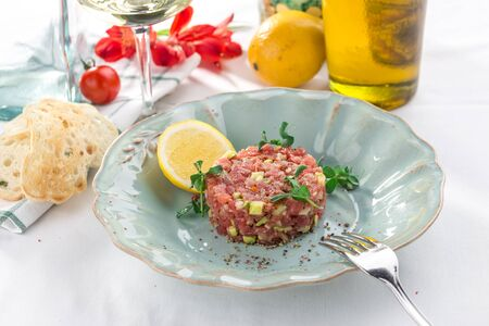 Photo pour Steak Tartare with bread toasts, lemon and cucumber on white table side view - image libre de droit