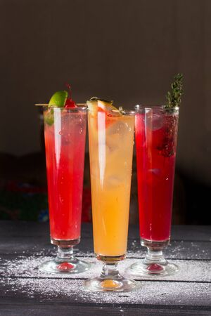 Photo for three glasses of fruit red yellow lemonade with ice in highball glasses on black background side view - Royalty Free Image