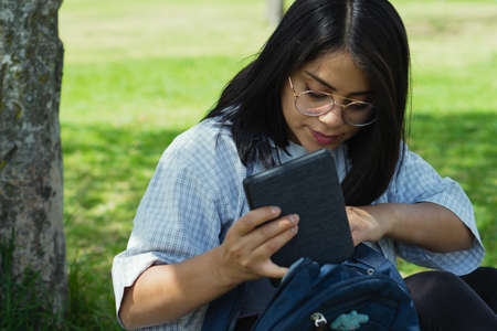 Photo pour Beautiful college student in a time of rest and reading in the park. - image libre de droit