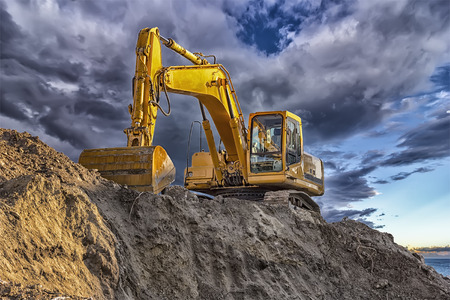 Photo for A stopping yellow excavator at an incredibly beautiful sunset - Royalty Free Image