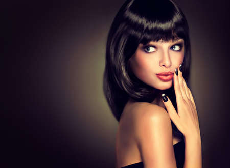 Surprised beautiful girl look away . Model brunette with hairstyle of the care. Black hair and a black manicure on the nails.Luxury fashion style, nails manicure, cosmetics ,make-up