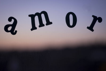 The word amor which means love in Spanish spelled in letters on a glass window pain with background of sunset sky and dark dusk landscape defocused in artistic effect in summer in Spain.