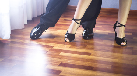 Male and female ballroom, standard, sport dance, latin and salsa couple dancers feet and shoes in dance academy school rehearsal room dancing salsa.
