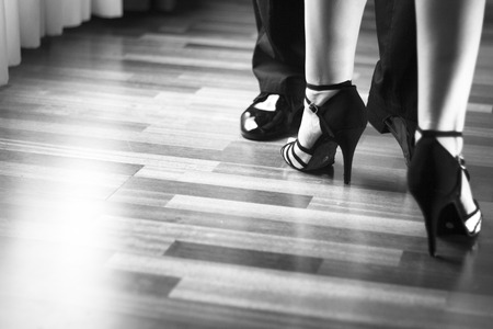 Foto de Male and female ballroom, standard, sport dance, latin and salsa couple dancers feet and shoes in dance academy school rehearsal room dancing salsa. - Imagen libre de derechos