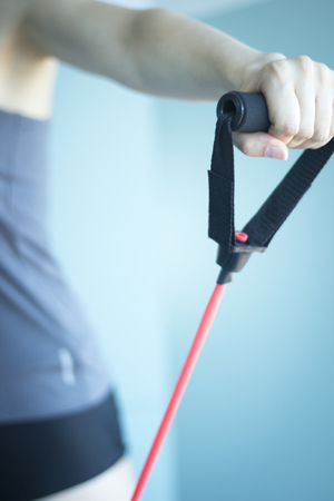 Woman with slim, fit and attractive body in 40's exercising with resistance exercise bands in gym shoulder exercise.