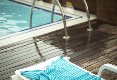 Hot summer by the outdoors swimming pool with wooden sundeck terrace.