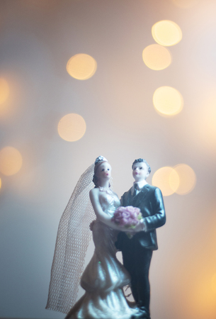 Foto de Wedding ceremony marriage bride groom cake topper figures with lights isolated. - Imagen libre de derechos