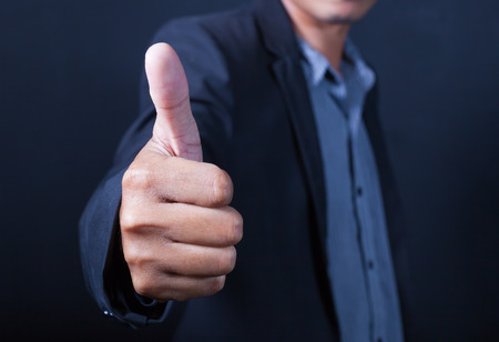 Hand of Asian businessman with thumbs up