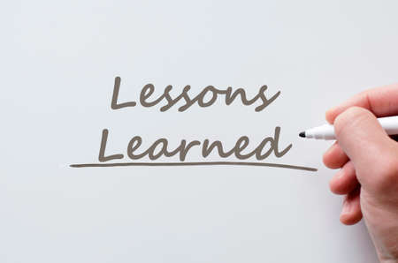 Human hand writing lessons learned on whiteboard