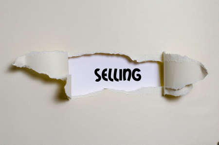 The word selling appearing behind torn paper
