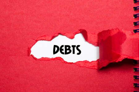 The word debts appearing behind torn paper