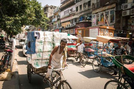 Delhi, India - September 18, 2014: Rickshaw carrying heavy cargo under the heat on the street of Old Delhi, India on September 18, 2014.