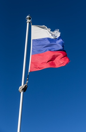 Tattered russian flag over blue sky background