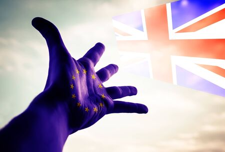 Hand with European Union Flag with Great Britain in the sky. Conceptual image.