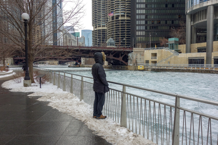 solitary person on Chicago riverwalk looking at icy river in winter