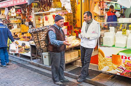 ISTANBUL, TURKEY - JANUARY 21, 2015: The conversation of the friends - merchant and buyer with the rustic basket on the back, next to the cheese stall, on January 21 in Istanbul.