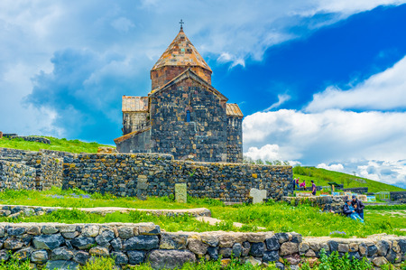 SEVAN, ARMENIA - MAY 31, 2016: The old Church of Holy Apostles of Sevanavank Monastery surrounded by stone fence, on May 31 in Sevan