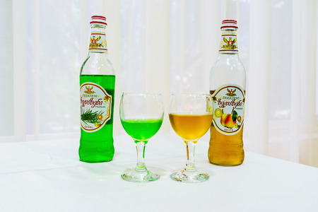 BORJOMI, GEORGIA - MAY 26, 2016: The different types of famous Georgian lemonades - tarragon and pear, in bottles and glasses on white background, on May 26 in Borjomi.