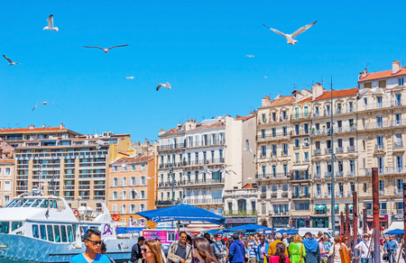 MARSEILLE, FRANCE - MAY 4, 2013: The seagulls fly over the crowded fish market and Vieux Port, on May 4 in Marseille.
